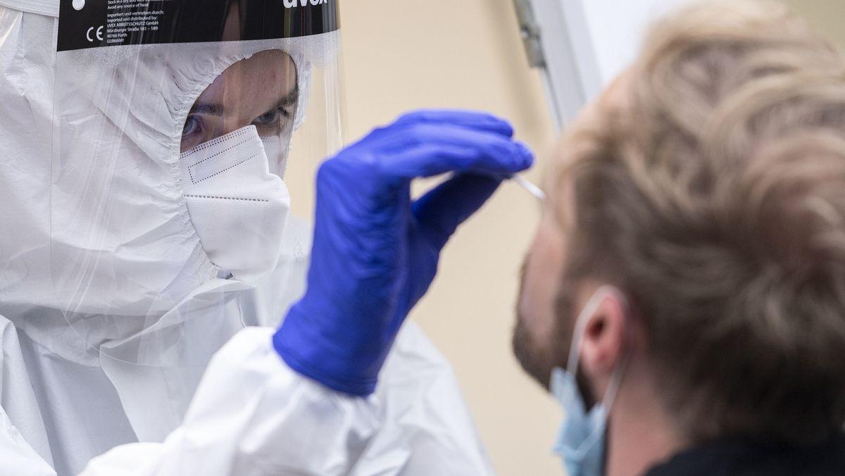 Mann bekommt einen Nasenabstrich an einer Corona-Teststation