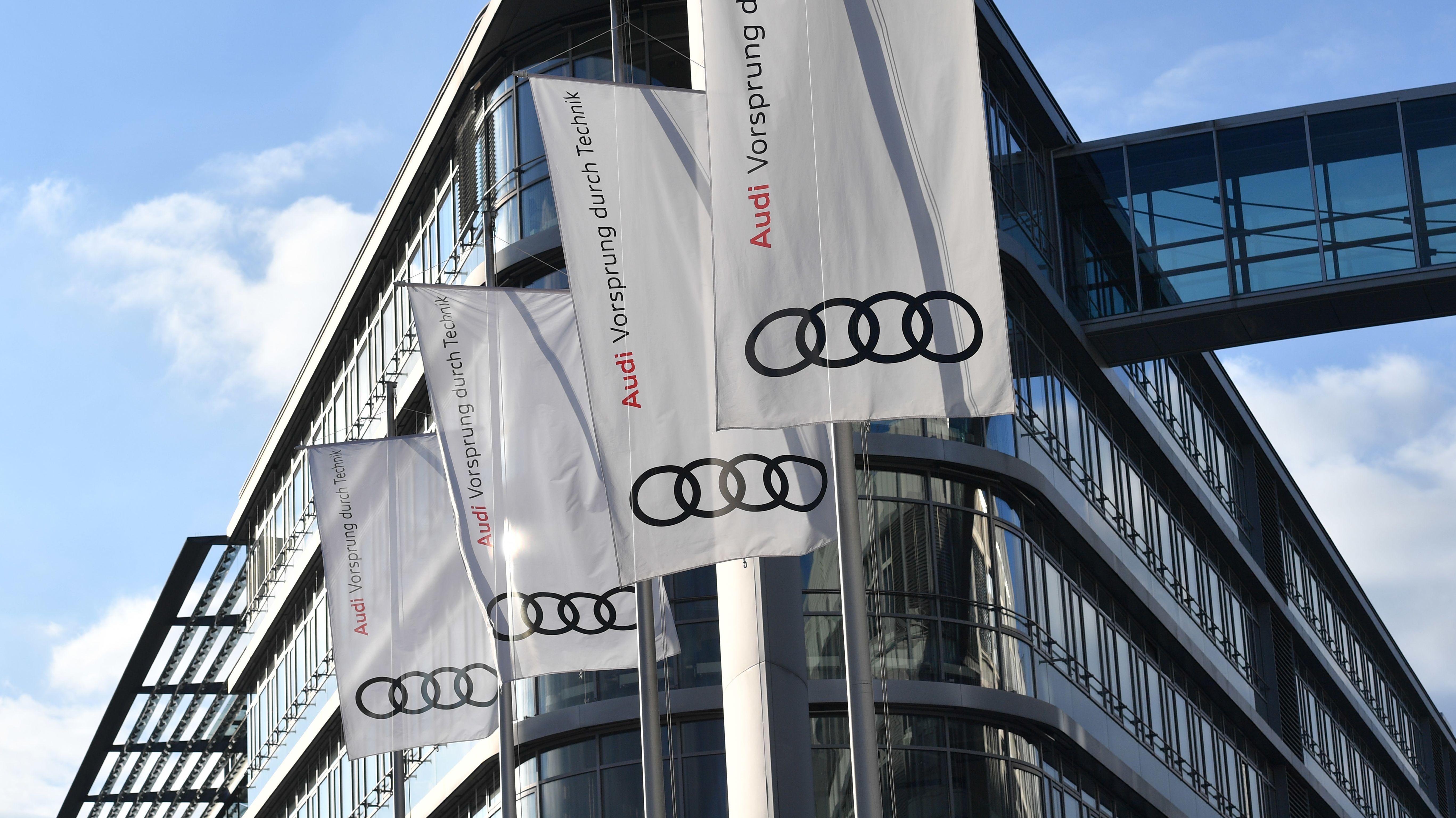 Fahnen mit Audi-Logo wehen an Masten vor der Unternehmensleitung
