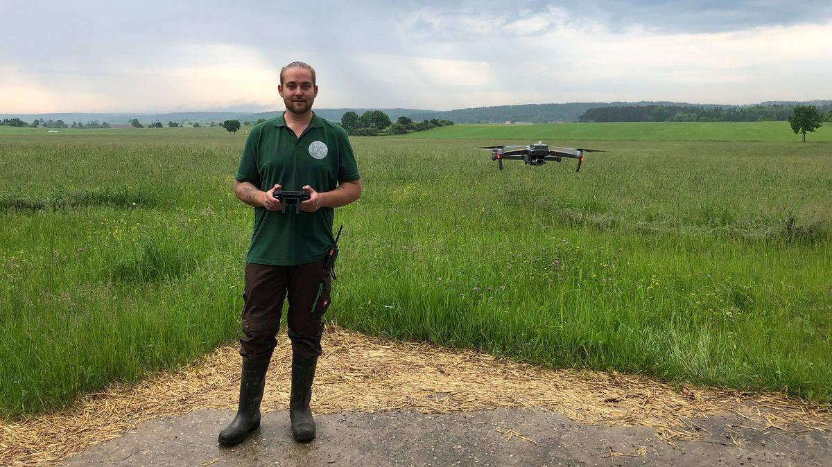Drohnenpilot Sascha Lagemann vor einer Wiese beim Start seiner Drohne mit Wärmebildkamera