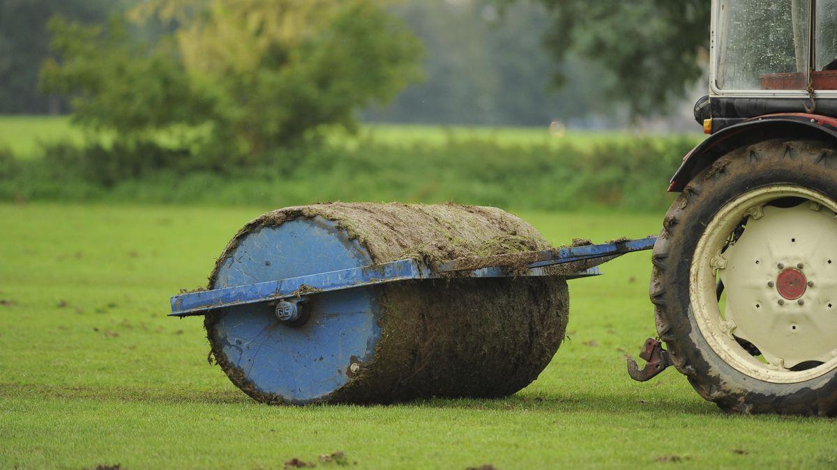 Eine Walze, um das Feld zu begradigen, zieht das nasse Gras ab.