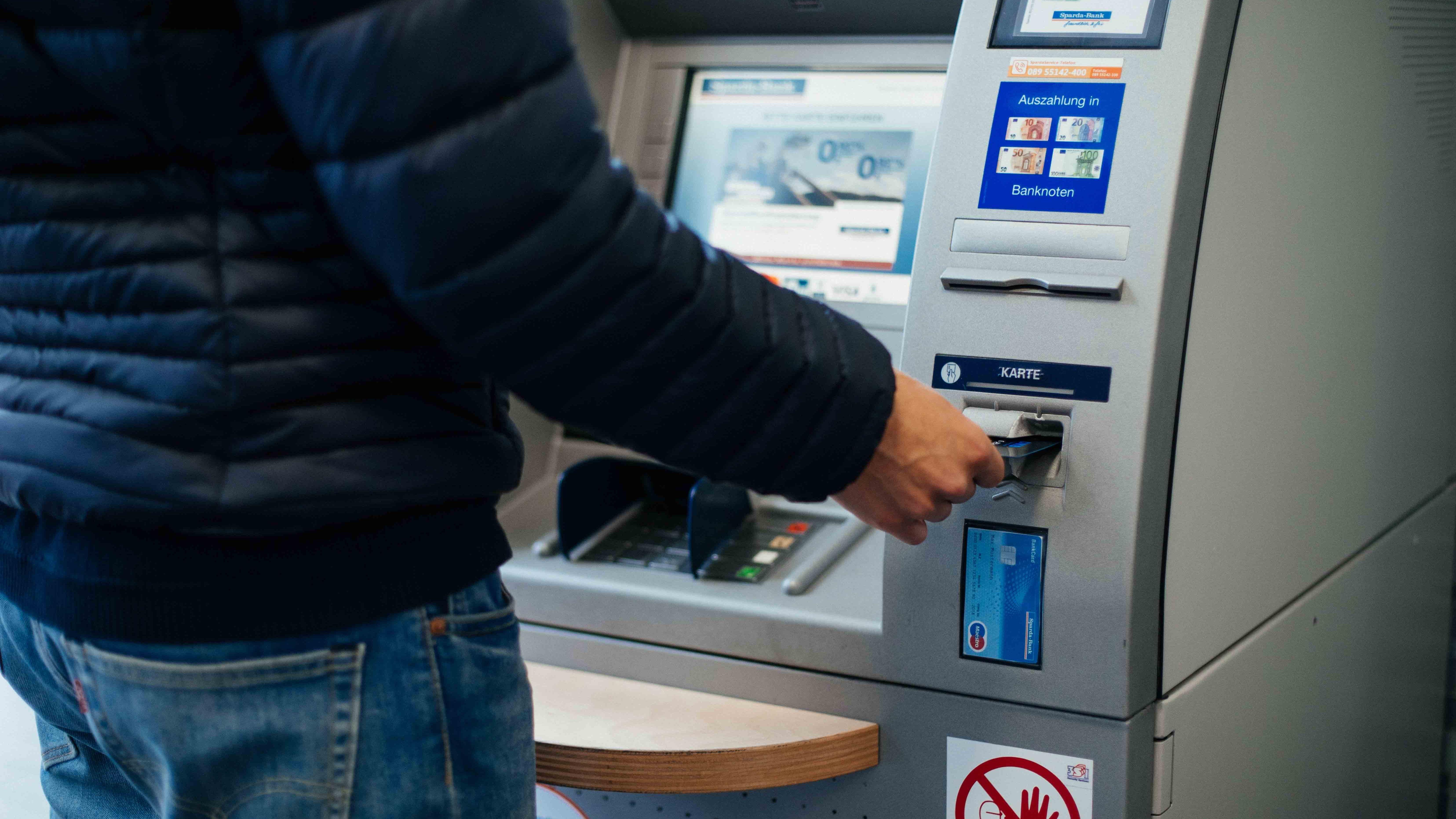 Ein Mann schiebt seine Bankkarte in den Geldautomaten.