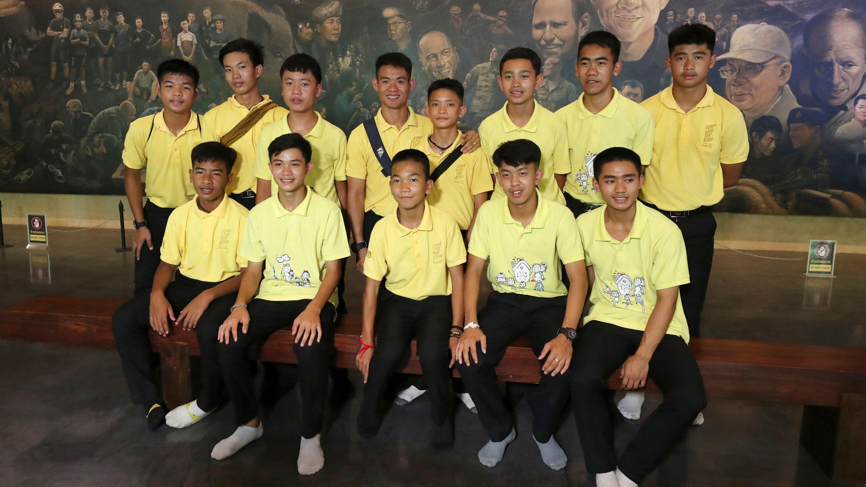 Die zwölf Jungs der thailändischen Fußballmannschaft  und ihr Fußballtrainer, die zusammen vor einem Jahr aus einer Höhle gerettet wurden.
