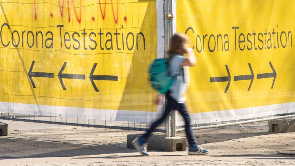 """München: Große gelbe Banner mit der Aufschrift """"Corona Teststation"""" hängen an Absperrgittern an der Theresienwiese in München."""