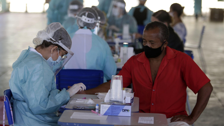 An einem Tisch sitzt ein Mann mit Maske, dem von einer Frau im Schutzanzug Blut abgenommen wird.