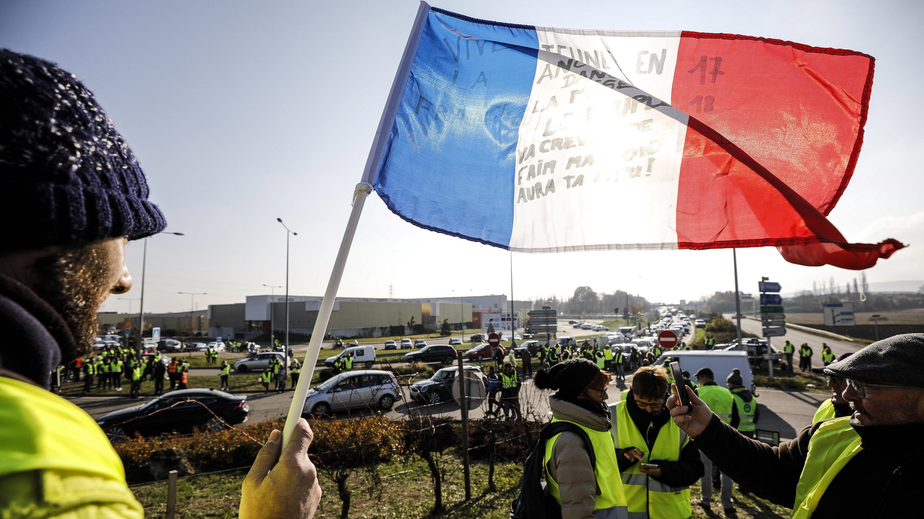 Demonstranten mit einer französischen Fahne blockieren im französischen Molsheim eine Straße, um gegen höhere Spritpreise zu demonstrieren.