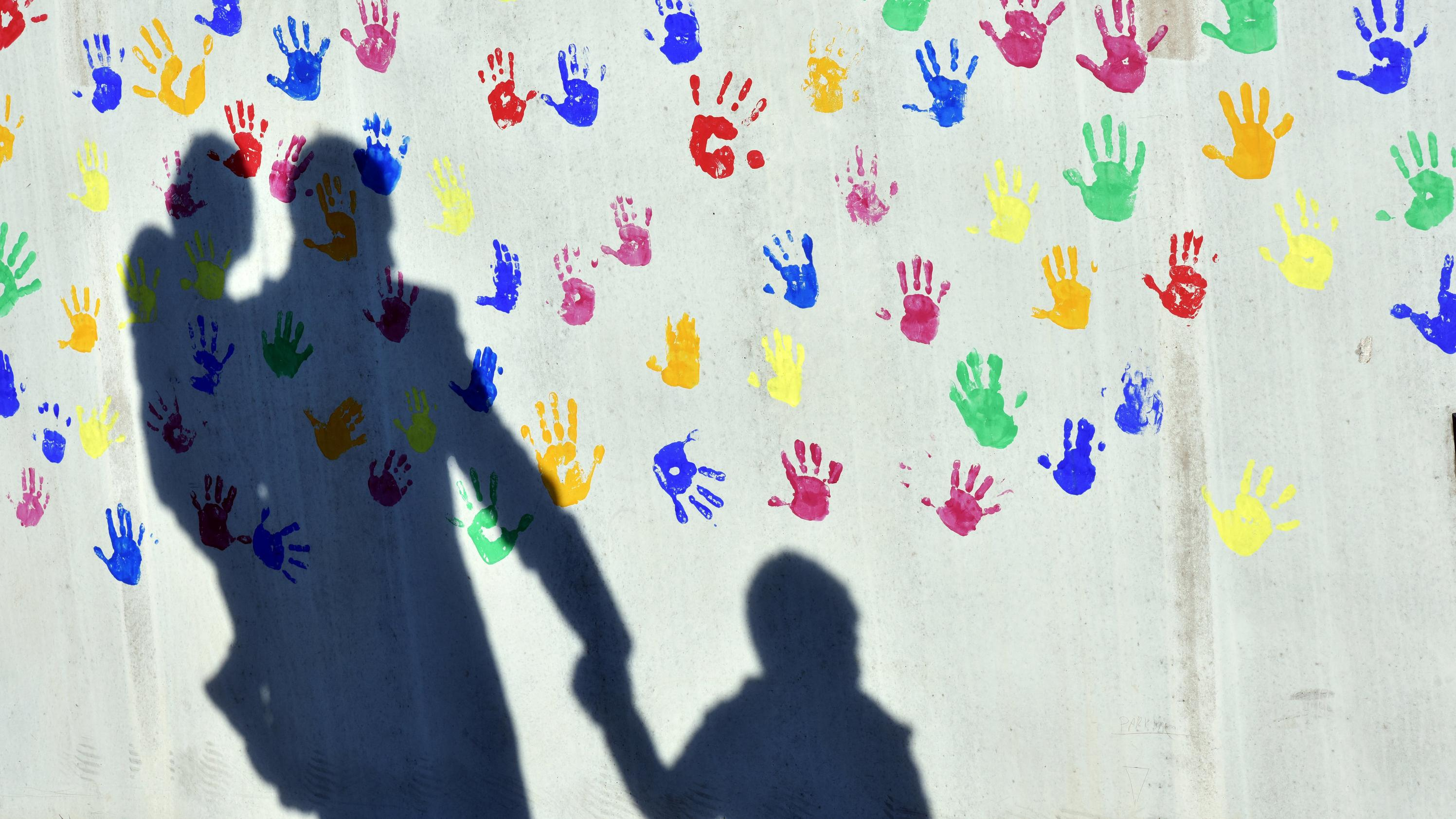 Schatten eines Mannes mit einem Kind auf dem Arm und einem weiteren Kind an der Hand