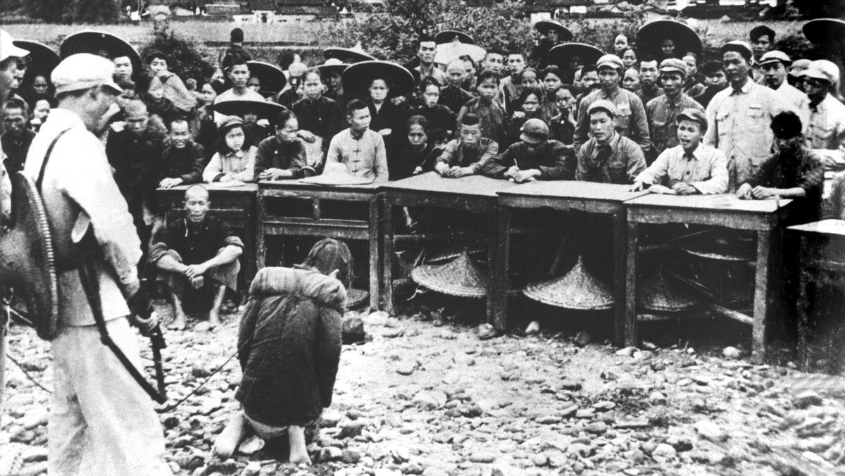 Gefesselt und schwer bewacht kniet der angeklagte Huang Chin-Chi im Januar 1953 vor einem sogenannten Volkstribunal in Fukang in der chinesischen Provinz Kwangtung, das im Freien über ihn Gericht hält. Ihm wird zur Last gelegt, das er Land besitzt. Zwischen 1950 und 1953 fand eine Neuverteilung des Grundbesitzes zugunsten der Bauern in der Volksrepublik China statt.