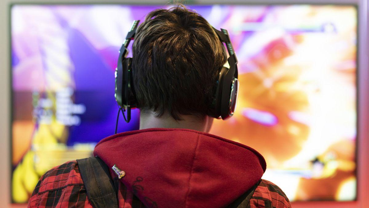 Teenager spielt auf einem großen Bildschirm ein Videospiel