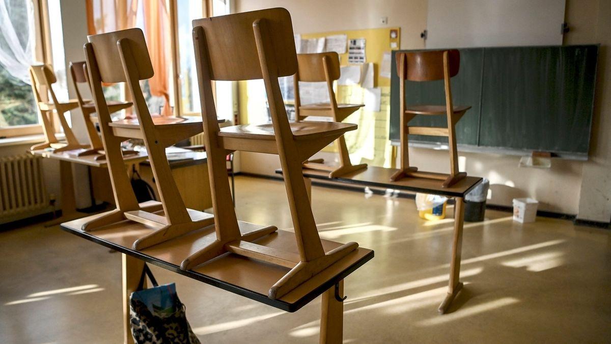 Stühle sind auf Schulbänke gestellt.