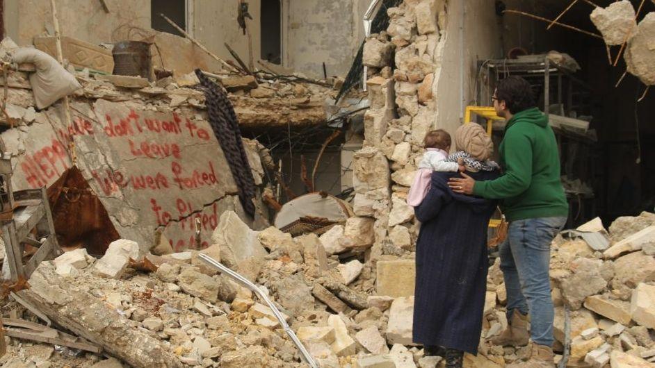 Ein Familie in Aleppo vor den Trümmern ihres zerstörten Hauses: Vater, Mutter, Baby
