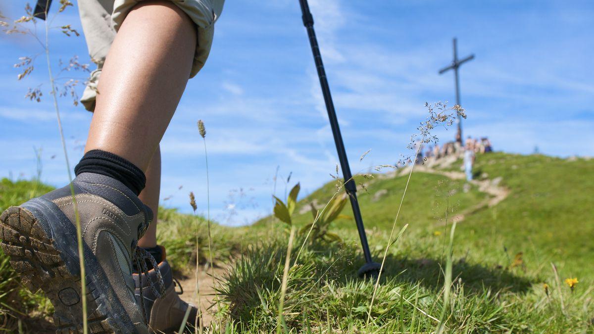 Beine, die in Wanderschuhen stecken, laufen auf einen begrünten Hügel mit Gipfelkreuz zu