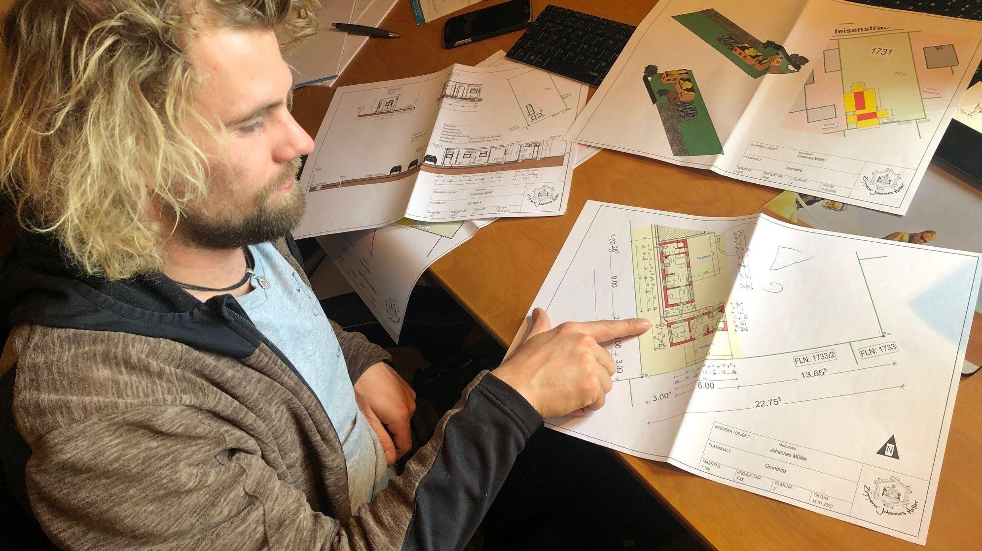 Zimmerer Johannes Müller mit den Plänen für zwei Modulbauhäuschen