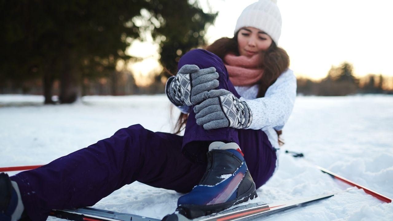 Frau umfasst sich das Bein nach einem Skiunfall