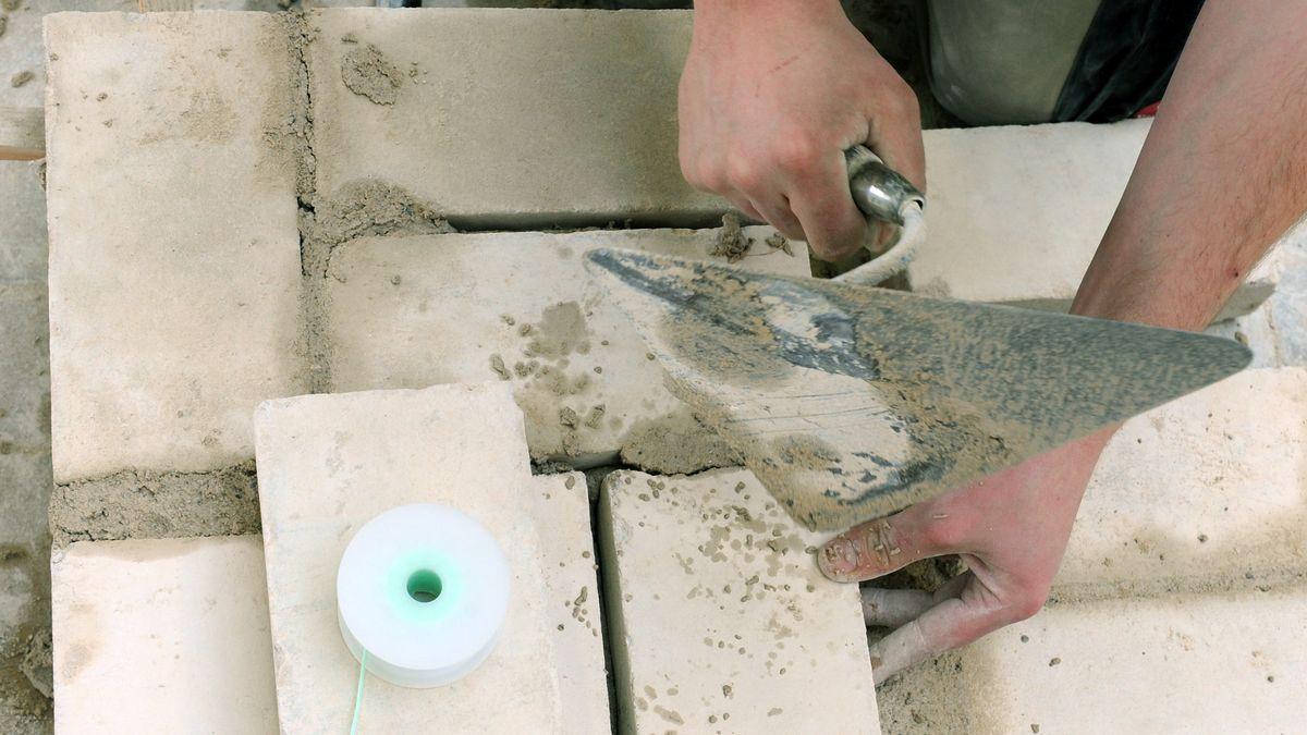 Ein Handwerker baut eine Mauer