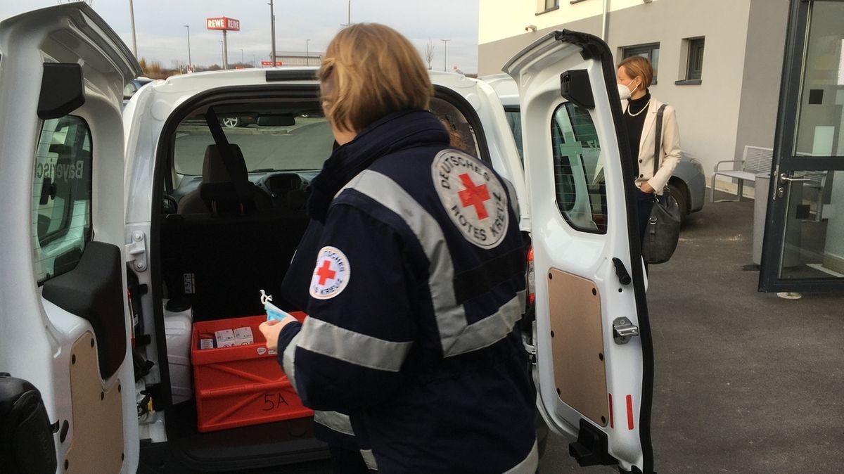 Eine Mitarbeiterin des BRK lädt den Corona-Impfstoff aus einem Auto aus.