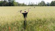Soundkünstler Marcus Maeder geht durch sehr hohes Gras und hält über seinem Kopf ein Mikrofon auf einem Stativ. | Bild:GEO/Christian Beutler