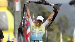 Anne Haug hält das Zielbanner der Ironman-Weltmesiterschaft auf Hawaii mit beiden Händen in die Höhe.   Bild:dpa-Bildfunk/Marco Garcia
