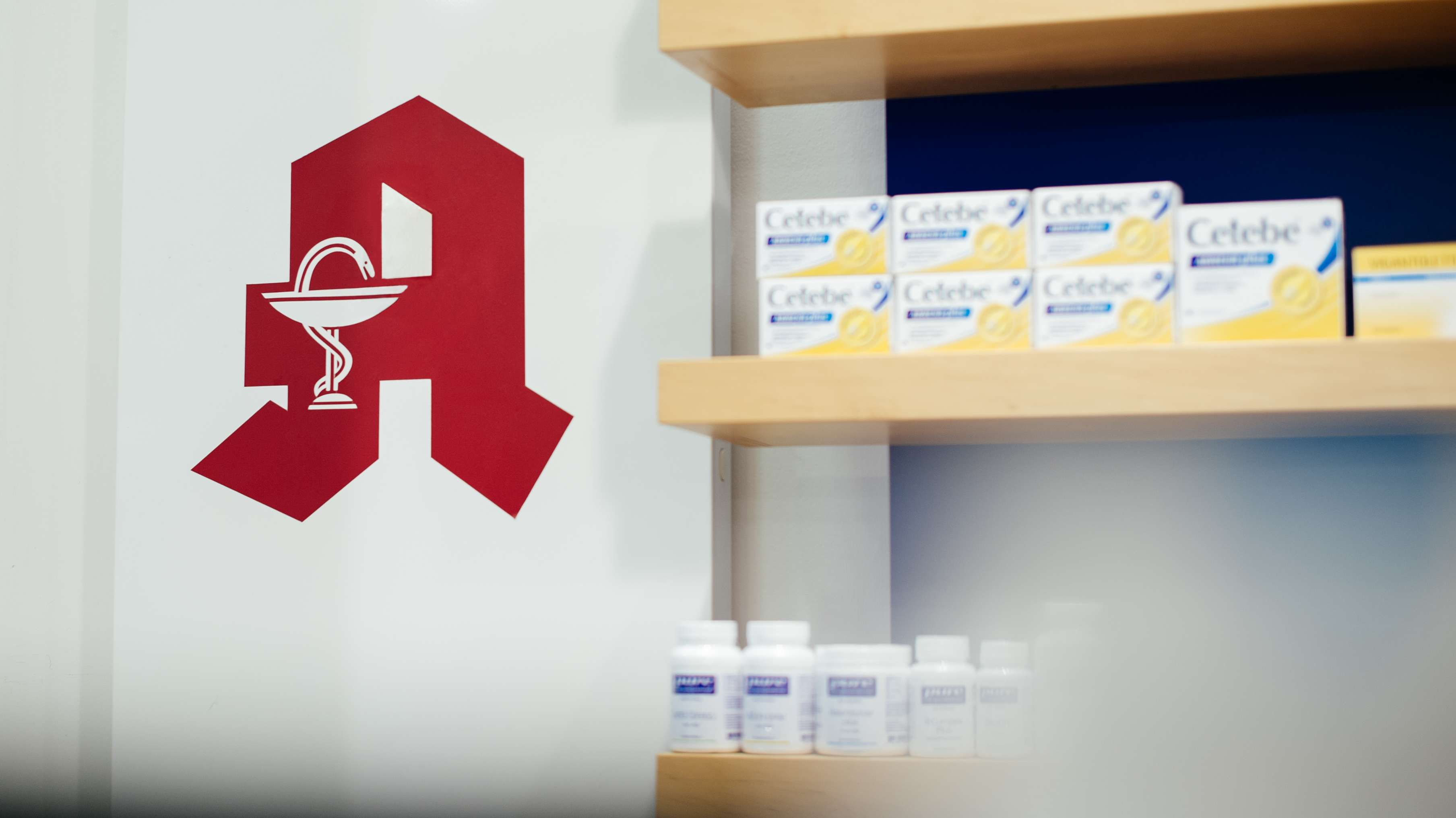 Das Logo einer Apotheke ist neben einem Regal mit Medikamenten zu sehen.