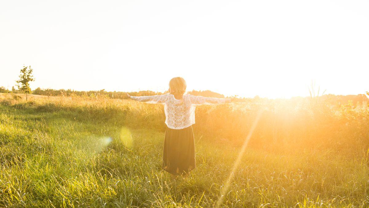 Frau im Sonnenuntergang auf Wiese