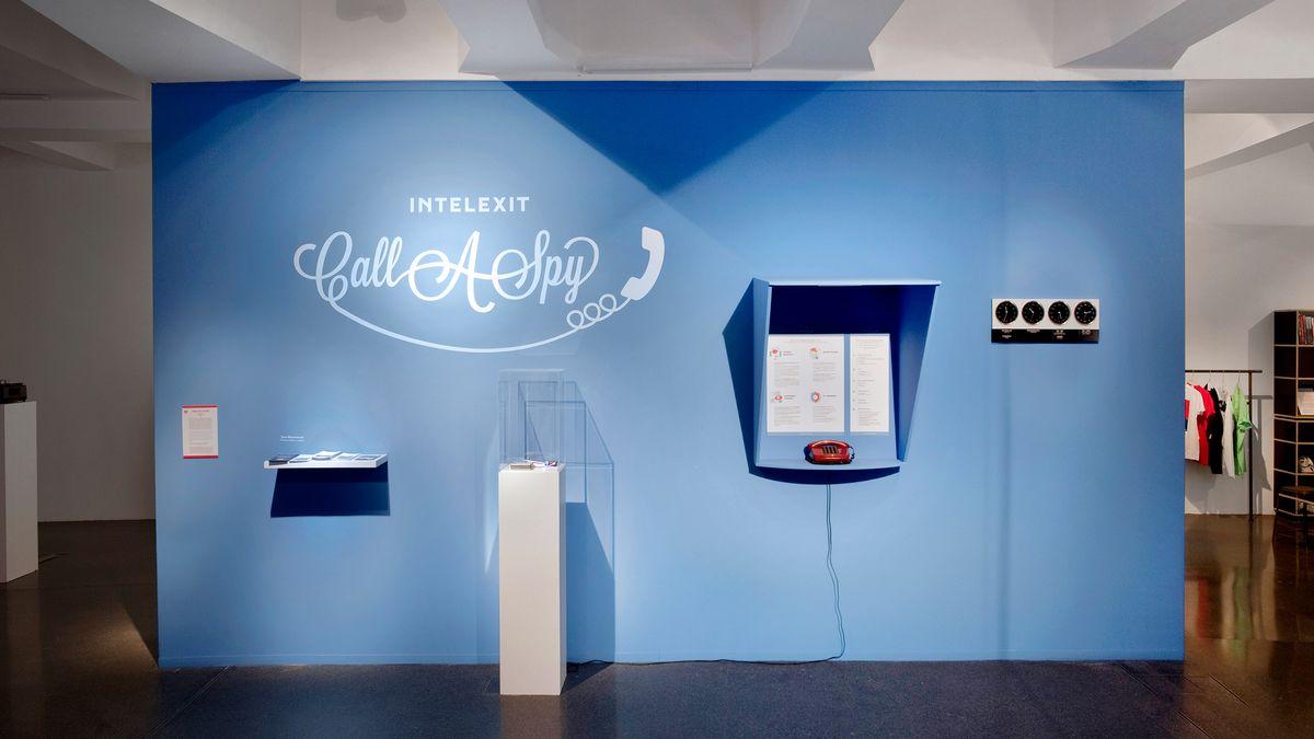 """Eine blaue Wand in einer Ausstellung mit der Aufschrift """"Call a Spy"""""""