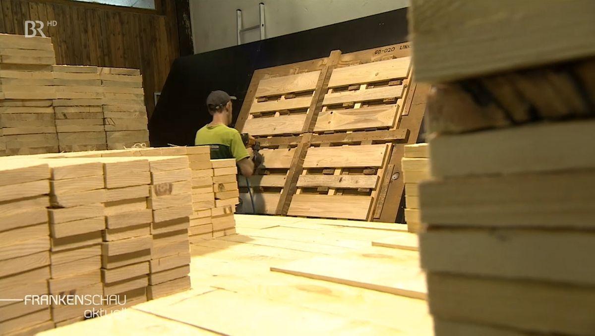 Ein Man verarbeitet Holzbalken und Bretter zu Paletten.