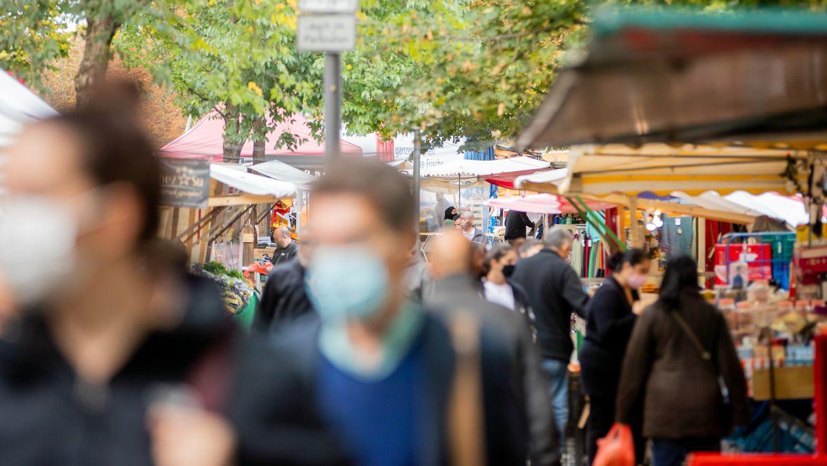 Menschen tragen Mund-Nasen-Bedeckungen und gehen in Berlin-Kreuzberg über den Markt am Maybachufer.