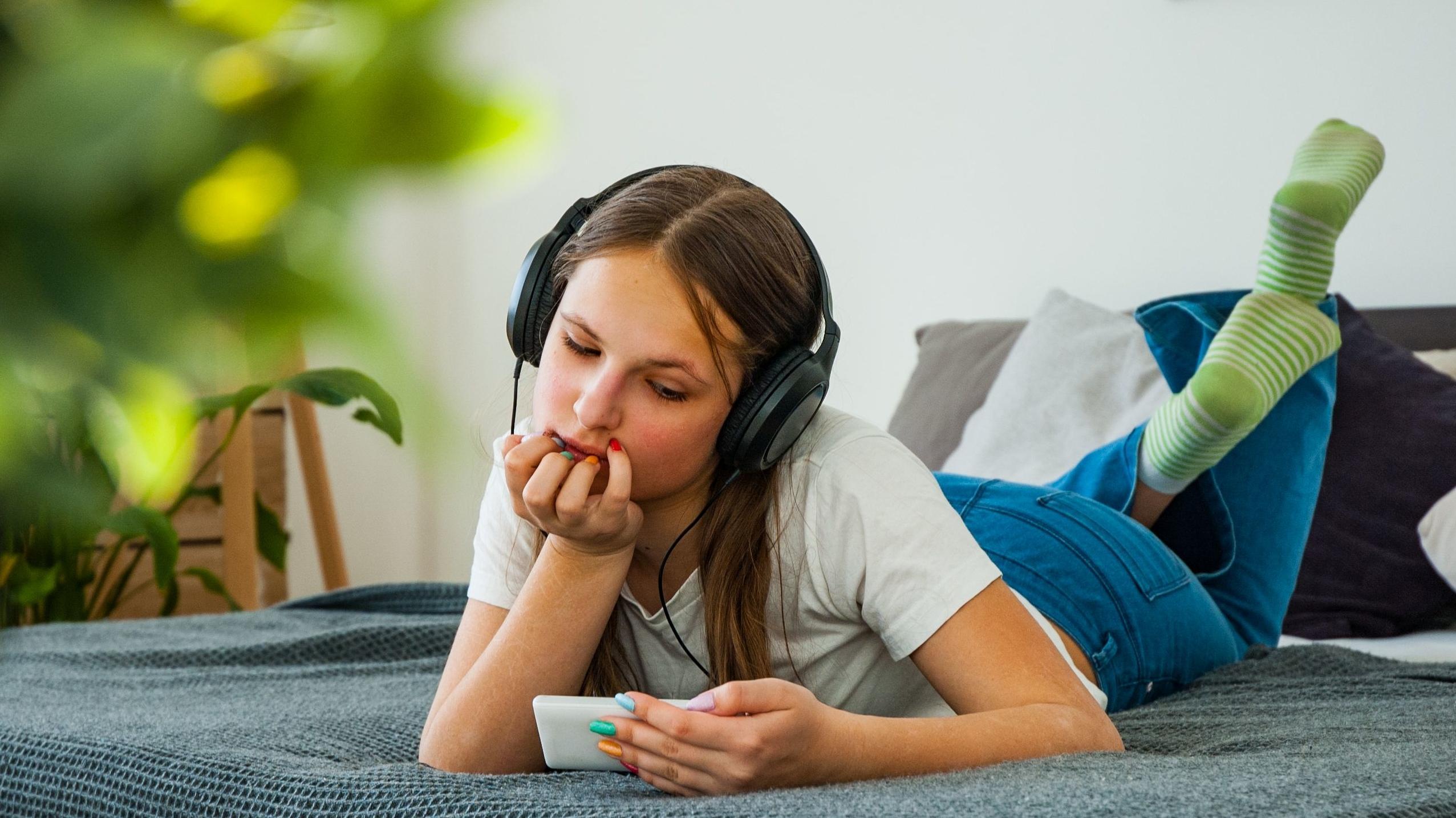 Mädchen liegt auf dem Bett und hört über Kopfhörer Inhalte vom Smartphone