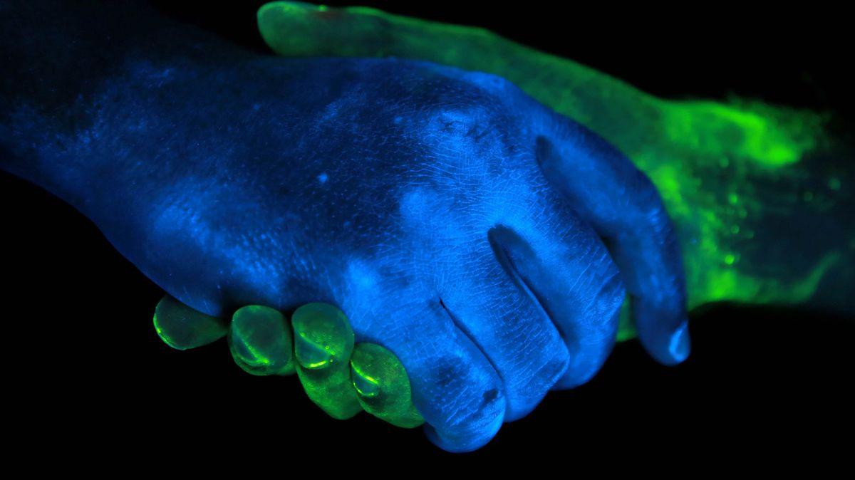 Handshake von zwei Händen im ultravioletten Licht.