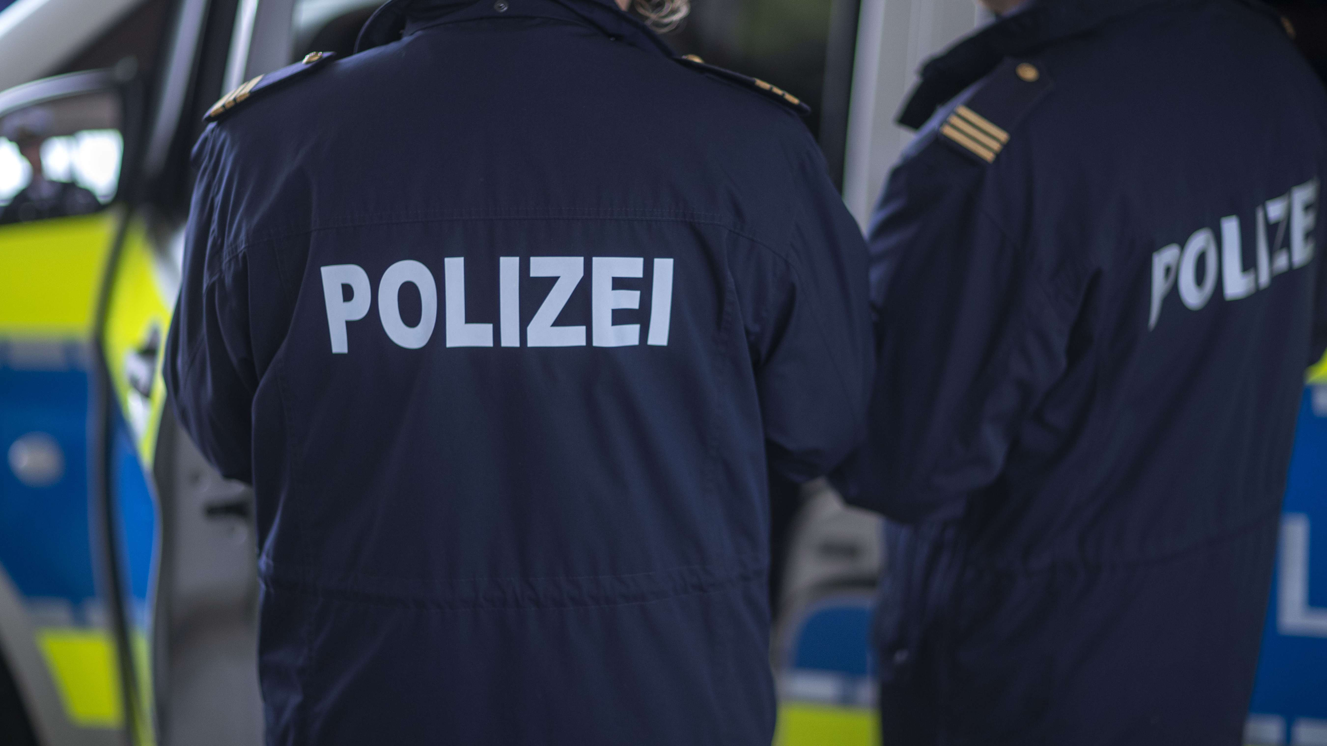 Symbolfoto: Polizisten vor einem Einsatzfahrzeug.