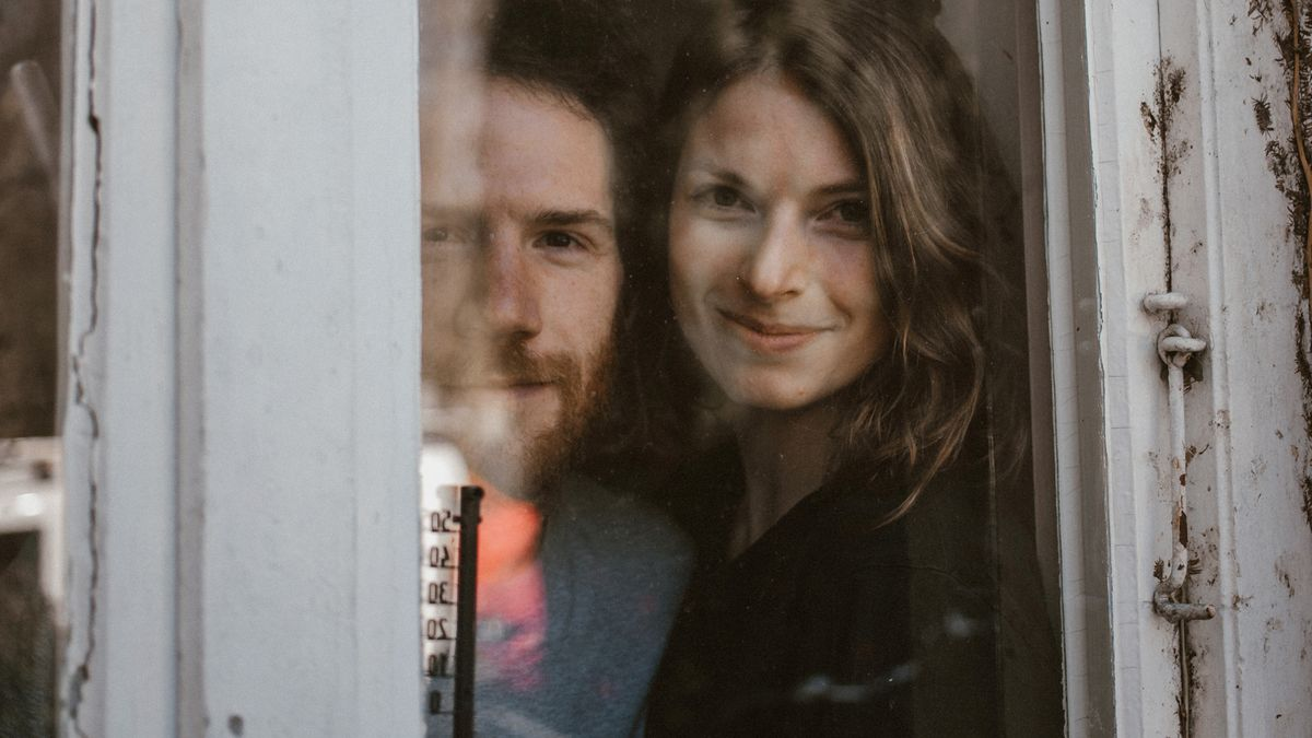 Ein junges Paar blickt durch ein schmales, altes Fenster nach draußen.
