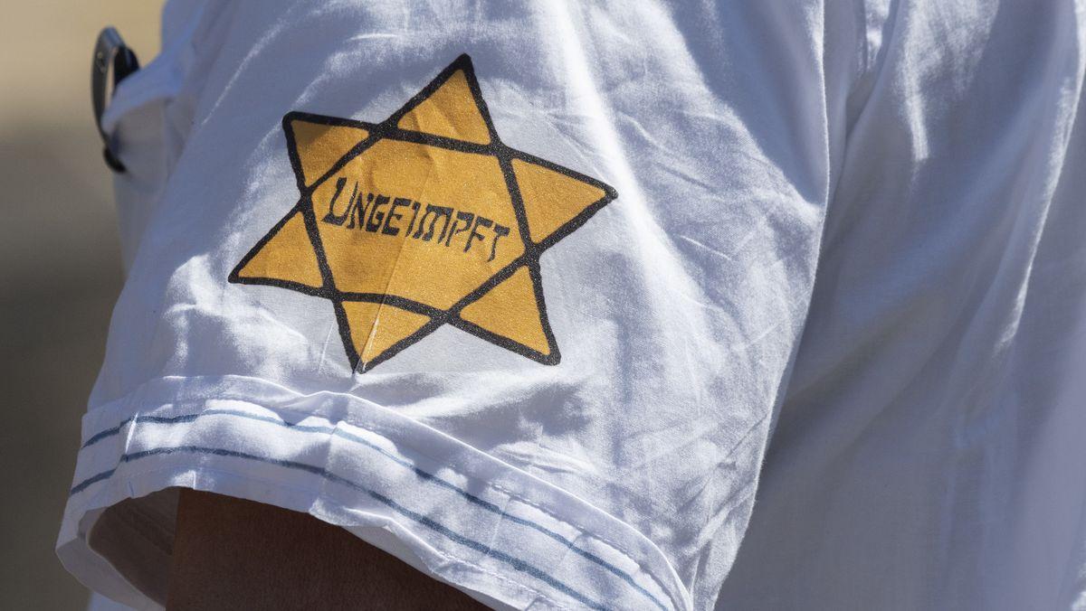 """Ungeimpft"""" steht auf dem einem David-Stern nachempfundenen Sticker am Arm eines Mannes, der versucht hatte, sich unter die Teilnehmer einer Demonstration zu mischen, die sich auch gegen Verschwörungstheorien zum Corona-Virus wendet."""