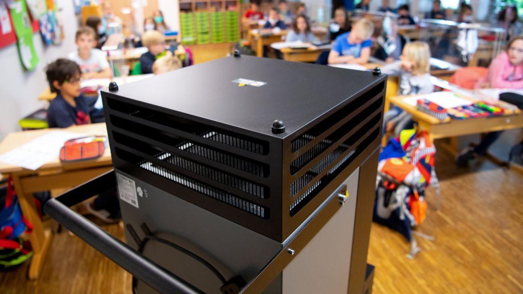 Der Fokus des Bildes liegt auf einem mehr als einen Meter hohen, viereckig und länglichen Luftfilter-Gerät, das in einer Grundschulklasse steht, die im Hintergrund in der Unschärfe auf ihren Plätzen im Klassenzimmer sitzt.