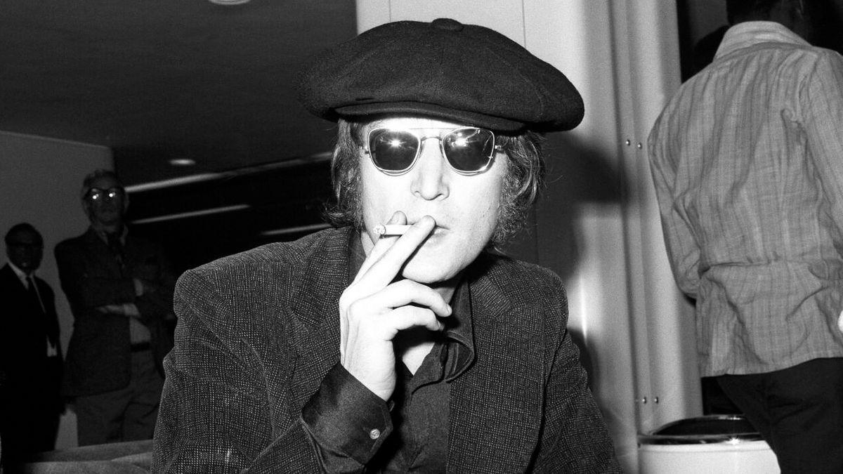 John Lennon mit Sonnenbrille und Schiebermütze sitzt, genüsslich an einer Zigarette ziehend, auf einem Sofa und schaut frontal in die Kamera.