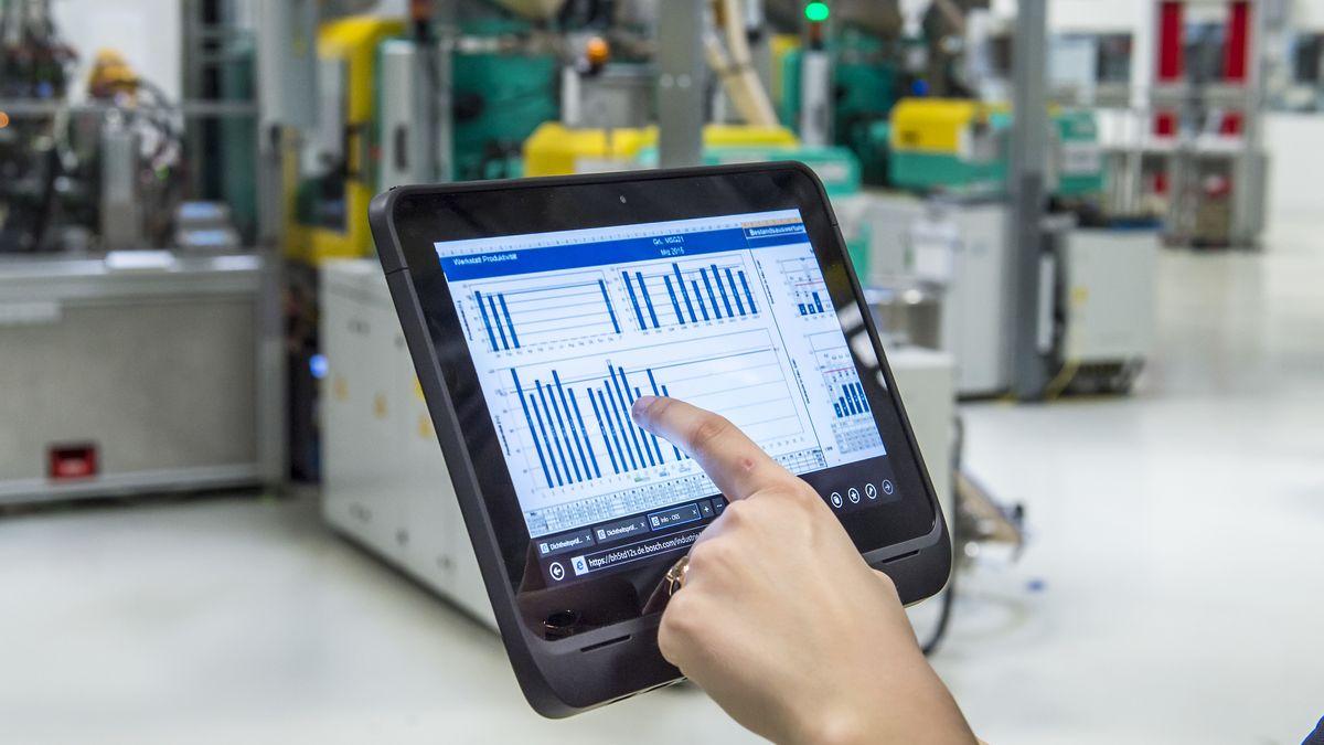 Eine Mitarbeiterin der Robert Bosch GmbH überprüft im Bosch Werk in Immenstadt mit einem Tablet die Betriebsdaten von vernetzten Maschinen.