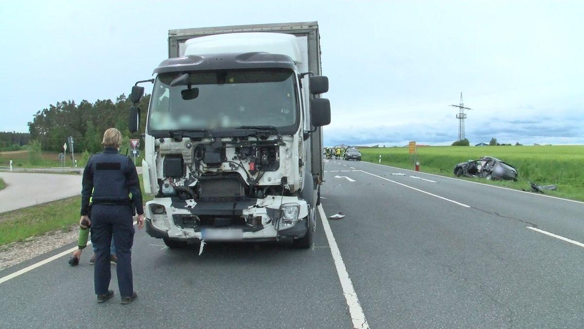 Ein Polizist vor einem Lkw mit kaputter Front auf der B14.