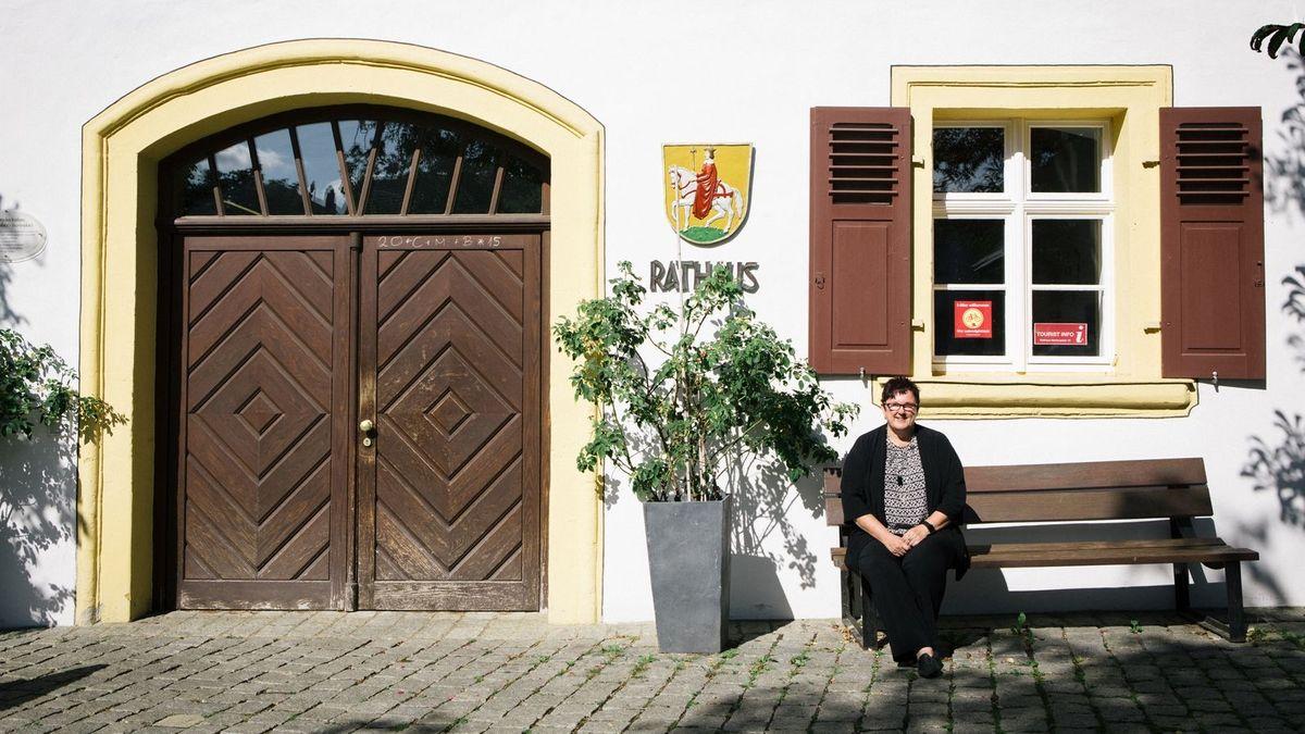 Die Bürgermeisterin von Hollfeld, Karin Barwisch, sitzt auf einer Bank vor dem Rathaus.