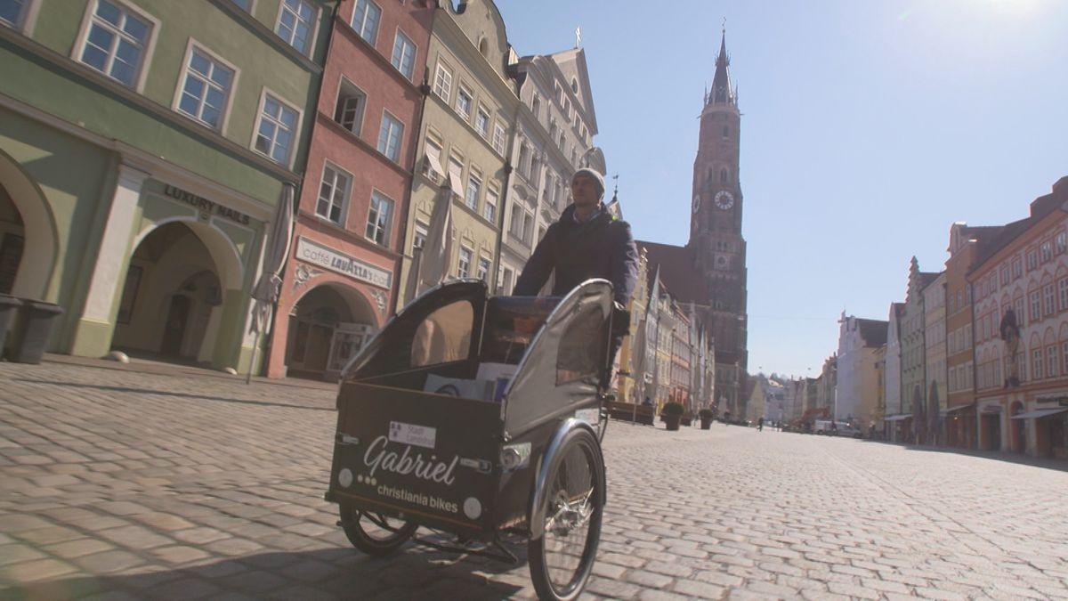 Wirtschaftsförderer der Stadt Landshut, Michael Luger, radelt mit einem Elektro-Lastenfahrrad durch die Einkaufsstraße