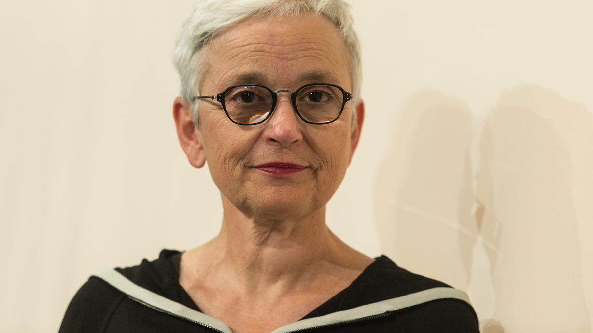 Barbara Mundel, Intendantin der Münchner Kammerspiele, blickt, vor einer hellen Wand stehend, in die Kamera