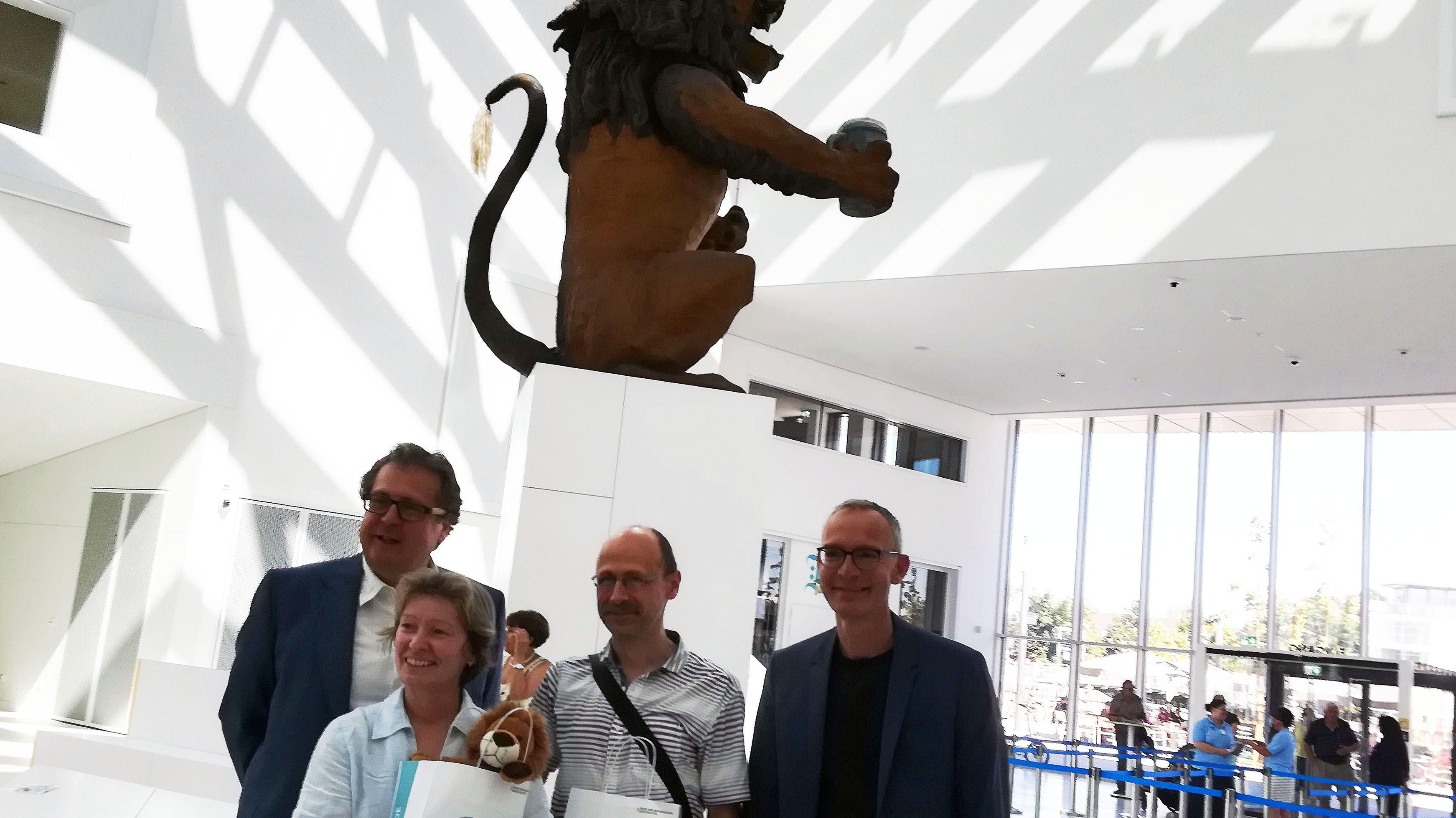 Richarl Loibl (li.) und BR-Moderator Chriostoph Süß (re.) begrüßen Sabine Stuber (2. v. li.) als 150.000 Besucherin im neuen Museum.