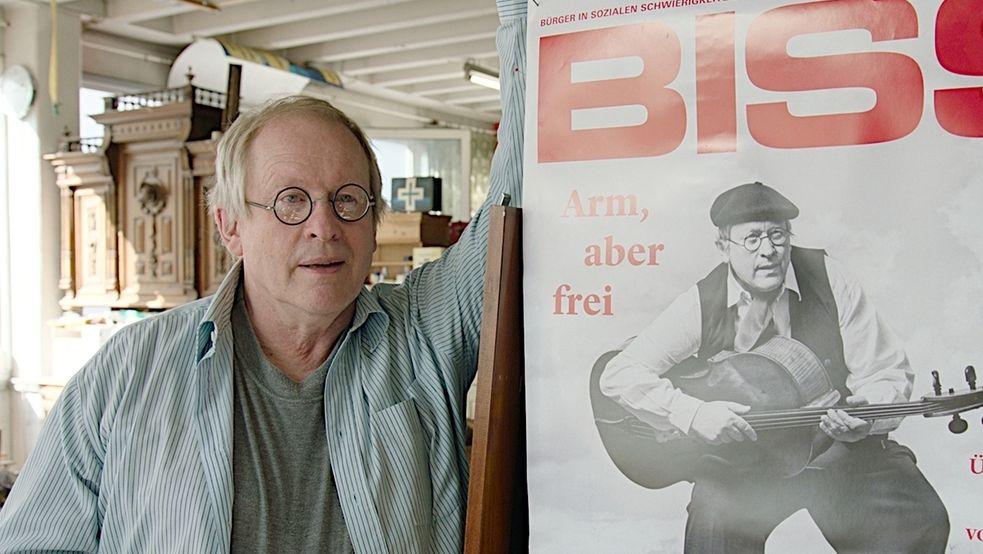 """Der Künstler Étienne Gillig steht neben dem Cover des BISS-Magazins: Das Titelbild zeigt ihn, wie er einen Kontrabass wie eine Gitarre hält. Die Unterschrift: """"Arm, aber frei"""""""