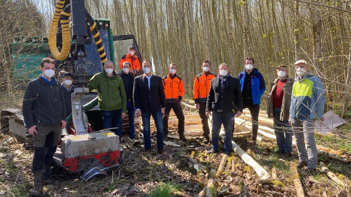 Die Projektpartner versammeln sich mit FFP2-Masken vor dem Harvester mit Entrindungskopf.