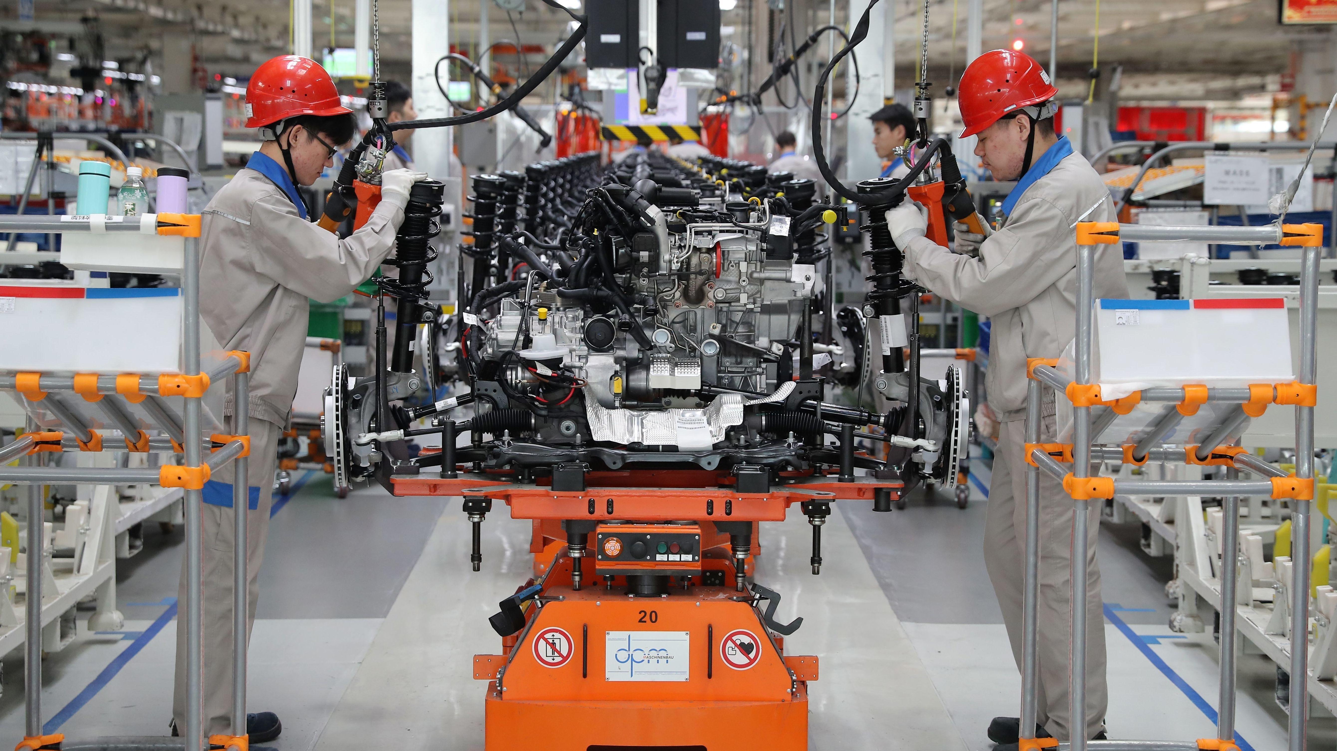 Beschäftigte arbeiten einem chinesischen Gemeinschaftsunternehmen von VW an einem Auto.