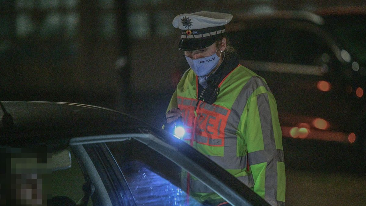 Eine Polizeibeamtin kontrolliert nachts einen Autofahrer, in der Hand hält sie eine Taschenlampe.