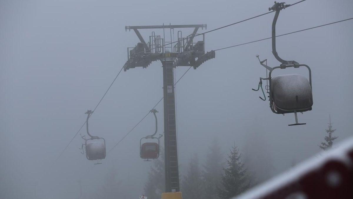 Eine Seilbahn steht still, im Hintergrund Fichten im Nebel.