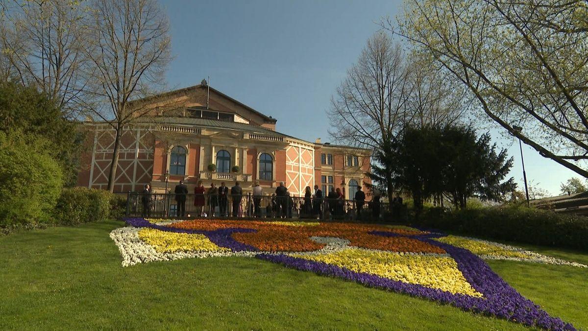 Das Bayreuther Festspielhaus mit Blumen im Vordergrund.