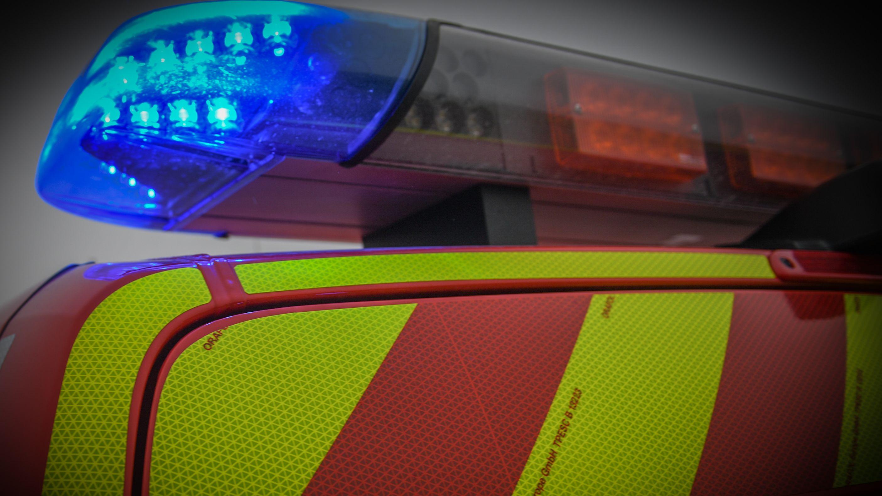 Ein Einsatzfahrzeug mit eingeschaltetem Blaulicht steht an einer Unfallstelle.
