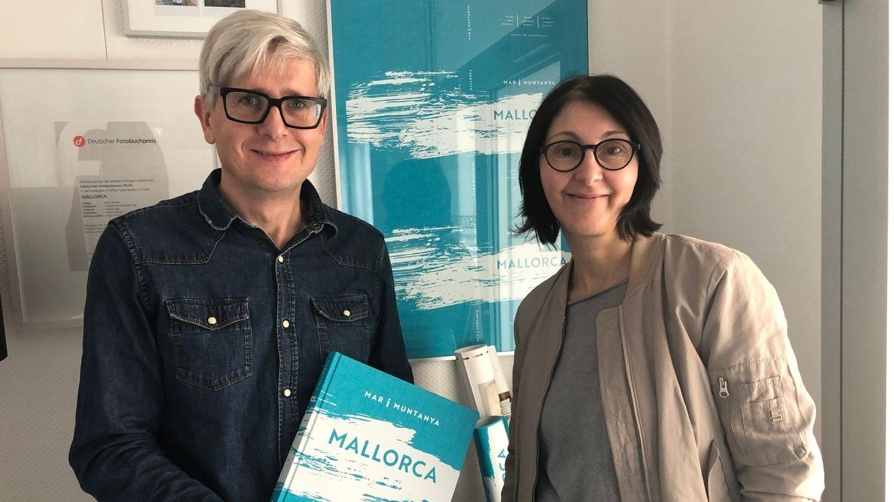 """Ein mann und eine Frau präsentieren ein türkisfarbenes Buch mit der Aufschrift """"Mallorca"""""""