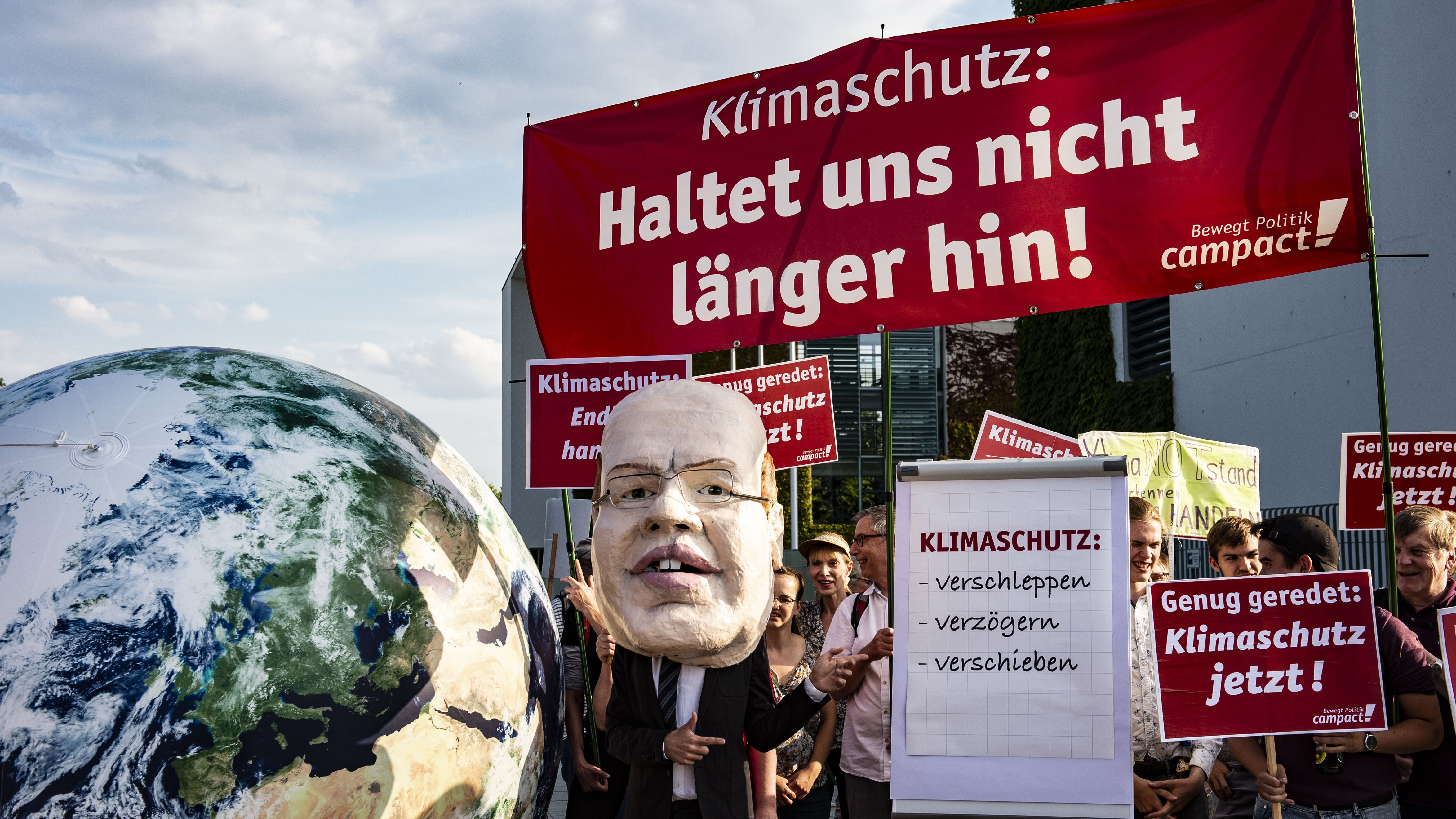 Demonstranten stehen Mitte Juli vor einer Sitzung des Klimakabinetts mit Transparenten und einer Maske von Bundeswirtschaftsminister Altmeier vor dem Bundeskanzleramt.