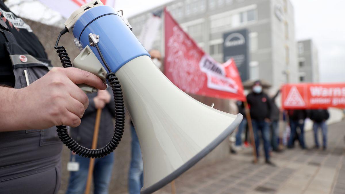 Ein Megaphon und Plakate beim Warnstreik der IG Metall (Symbolbild).
