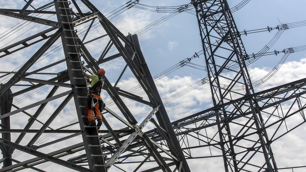 Arbeiter an einem Strommast | Bild:picture alliance / R. Goldmann